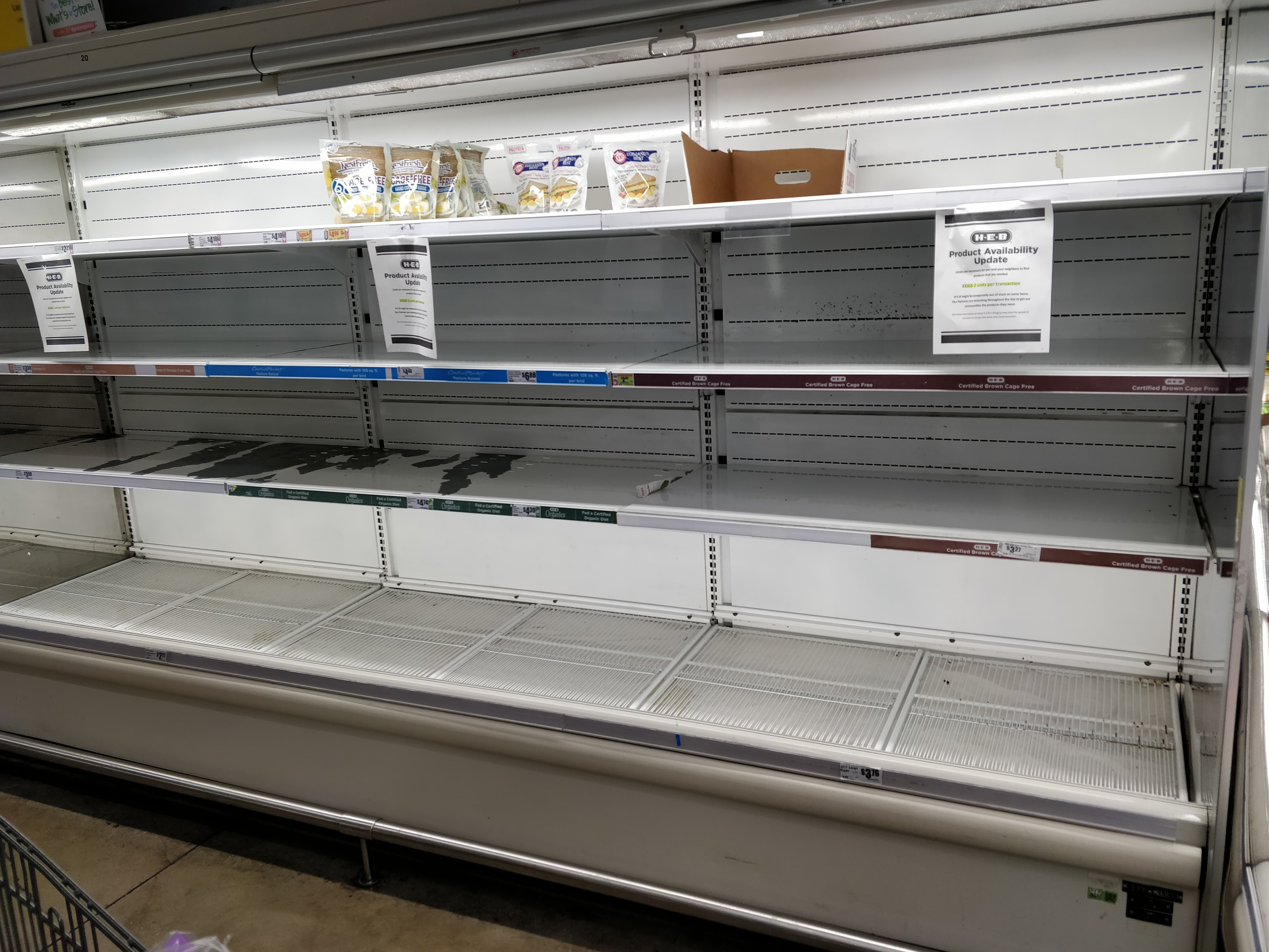 grocery store with empty cooler shelves March 2020